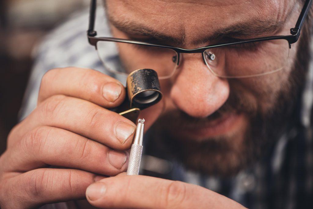man examining jewelry